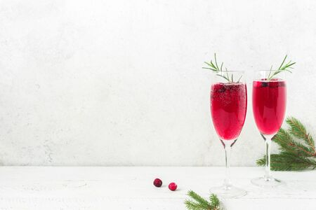 Cranberry mimosa with rosemary and Christmas decor on white background, copy space. Cocktail with champagne for Christmas morning. Banco de Imagens