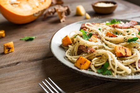 Pumpkin and Bacon Pasta with grated parmesan cheese. Homemade spaghetti pumpkin pasta on wooden, close up. Seasonal autumn food. Pasta Pumpkin Carbonara.