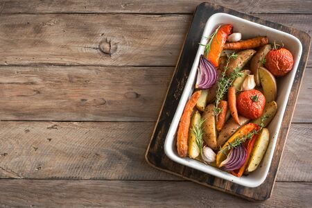 Oven roasted vegetables with spices and herbs in baking dish on wooden, top view, copy space. Vegetarian organic autumn meal - baked vegetables. Banco de Imagens