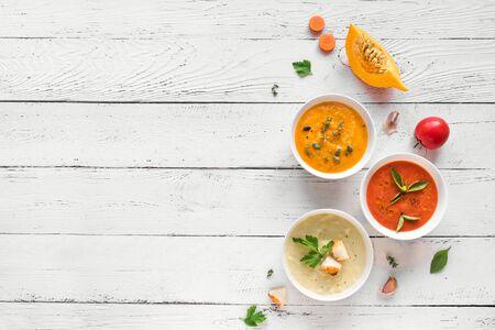 Vegetable Soups. Set of various seasonal vegetable soups and organic ingredients, top view, copy space. Homemade colorful vegan vegetarian soups. Banco de Imagens
