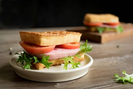 Savory waffle sandwich with ham and tomato for keto breakfast. Chaffle (cheese and egg waffle) sandwich on dark table,  copy space.