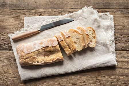 Ciabatta - Fresh Homemade Italian Bread sliced on napkin, wooden table, top view.