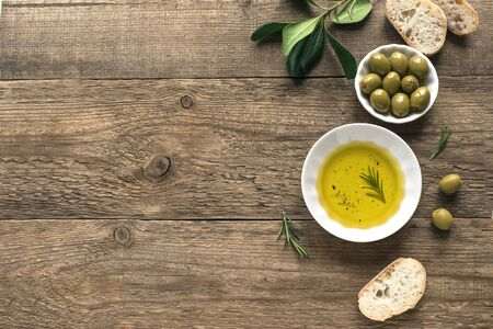 Olive Oil. Organic olive oil  in bowl with green olives, rosemary and ciabatta bread on wooden background ,top view, copy space. Healthy mediterranean food concept. Stok Fotoğraf