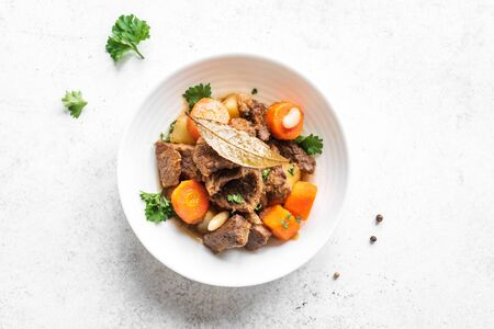 Beef meat stewed with potatoes, carrots and spices on white background, top view, copy space. Homemade winter comfort food - slow cooked meat stew. Reklamní fotografie