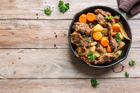 Beef meat stewed with potatoes, carrots and spices on wooden background, top view, copy space. Homemade winter comfort food - slow cooked meat stew.