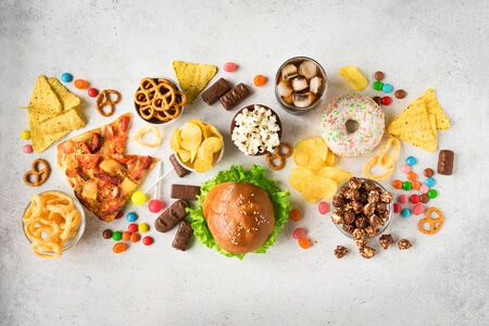 Set of Unhealthy Food on white, top view, copy space. Unhealthy eating, junk food or TV snacks concept. Stock Photo