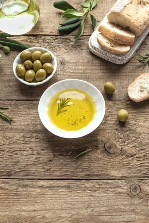 Olive Oil. Organic olive oil  in bowl with green olives and ciabatta bread on wooden background , top view, copy space.  Healthy food concept. Stok Fotoğraf