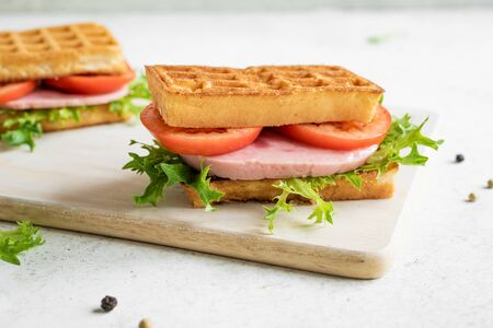 Cheese waffle sandwich with ham and tomato for keto breakfast. Chaffle (cheese and egg waffle) sandwich on white,  close up. 写真素材