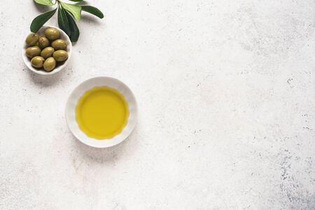 Olive Oil. Organic olive oil with green olives in bowl on white stone background with copy space, healthy food concept. Stok Fotoğraf