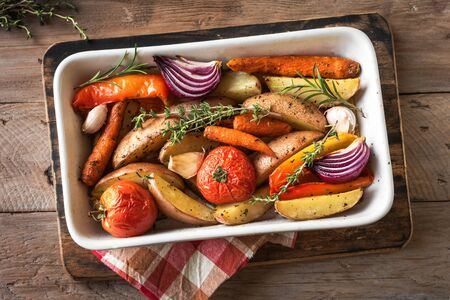 Oven roasted seasonal vegetables with spices and herbs in baking dish, top view, copy space. Vegetarian vegan organic autumn meal - baked vegetables. Reklamní fotografie