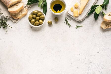 Mediterranean food background. Fresh italian ciabatta bread with herbs, olive oil, balsamic vinegar, parmesan and olives on white background, top view, copy space.