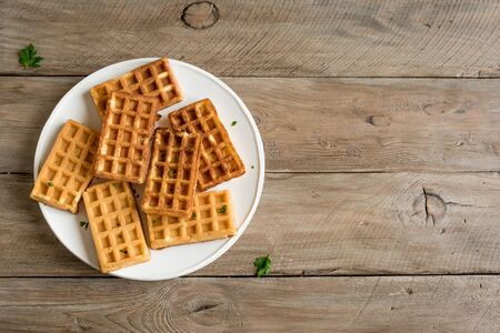 Savory egg and cheese waffles (chaffles) for breakfast. Keto (ketogenic) recipe - morning protein waffles, top view, copy space.
