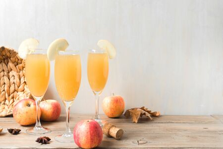 Apple Mimosa Cocktail on wooden table, copy space. Seasonal autumnal drinks for Thanksgiving holidays - champagne mimosa cocktail with apples.