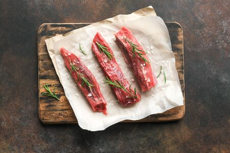 New York Strip Steak with salt and rosemary on dark background, top view, copy space. Uncooked raw beef strip steaks.