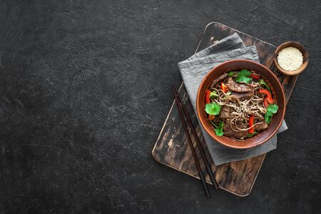 Stir fry with soba noodles, beef (meat) and vegetables. Asian healthy food, stir fried meal in bowls on black background, top view, copy space. Stock fotó