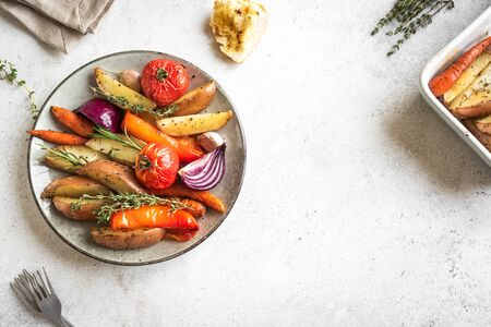Oven roasted seasonal vegetables with spices and herbs on white, top view, copy space. Vegetarian vegan organic autumn meal - baked vegetables.