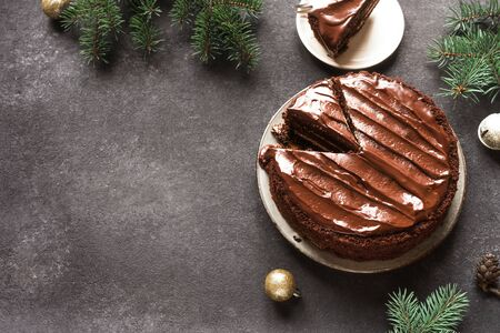 Chocolate Christmas Cake on dark background, top view, copy space. Classic chocolate cake with dark chocolate and Christmas fir branches.