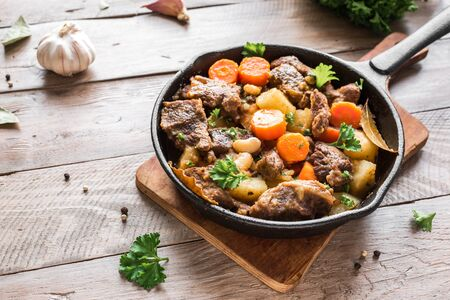 Beef meat stewed with potatoes, carrots and spices on wooden background, copy space. Homemade winter comfort food - slow cooked meat stew.
