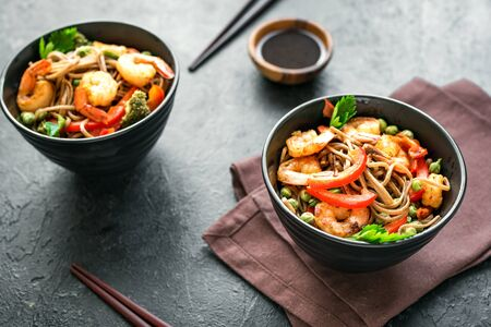 Stir fry with soba noodles, shrimps (prawns) and vegetables. Asian healthy food, stir fried meal in bowls over black background, copy space.