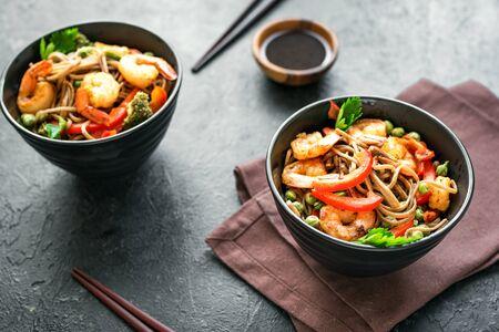 Stir fry with soba noodles, shrimps (prawns) and vegetables. Asian healthy food, stir fried meal in bowls over black background, copy space.