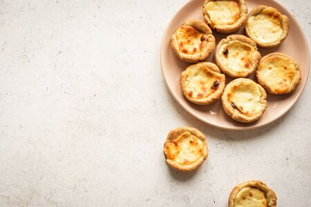 Pastel de Nata Portugese egg custard pies on white background, top view, copy space.