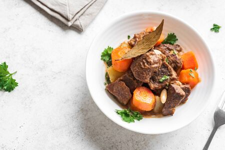 Beef meat stewed with potatoes, carrots and spices on white background, close up. Homemade winter comfort food - slow cooked meat stew.