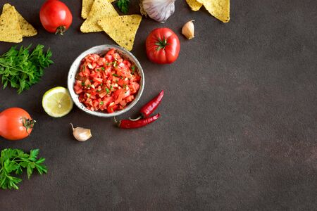 Hot mexican salsa sauce and ingredients on black background, top view, copy space. Homemade spicy salsa sauce or dip. Reklamní fotografie