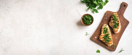 Grilled Chicken or Turkey Breast with green Chimichurri Sauce, copy space, banner. Homemade Chicken or Turkey Breast Steak with fresh herbs.