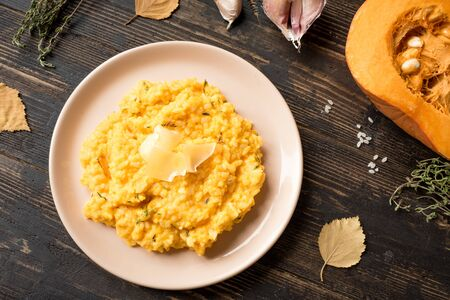 Pumpkin Risotto with thyme and parmesan cheese on dark wooden table, top view. Seasonal autumnal recipe - risotto with organic pumpkins. 写真素材 - 132048723