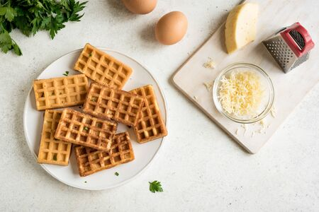 Chaffles - egg and cheese waffles for breakfast. Keto (ketogenic) recipe - morning savory protein waffles and ingredients, top view, copy space.
