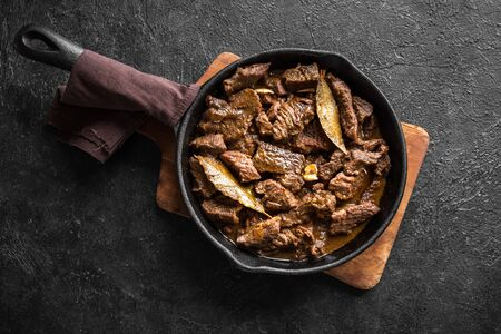Meat Stew. Beef stewed in red wine sauce, top view, copy space. Roasted beef meat. Braised beef portion meat. Slow cooked beef meat in cast iron pan. Stock fotó