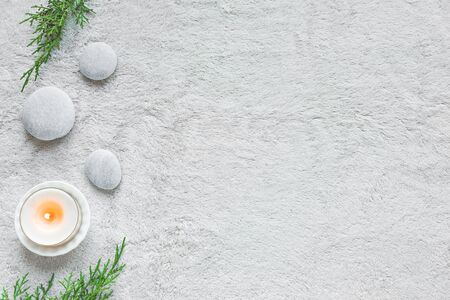 Spa concept on white soft towel background, green leaves, candle and zen like stones, top view, copy space.