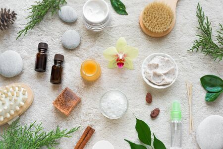 Natural Skin Care and Spa Set on white soft towel background with natural cosmetic products, flower, green leaves, candle and zen like stones. Relax concept, top view, flat lay.