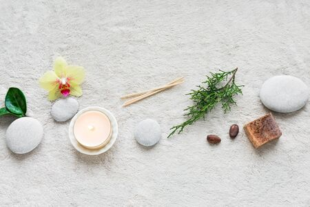 Spa Set on white soft towel background with natural cosmetic products, flower, green leaves, candle and zen like stones. Skin care and relax concept, top view, copy space.