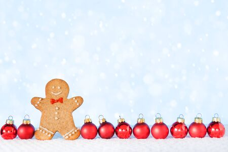 Christmas composition with Gingerbread man on white background. Trendy Christmas minimal concept - homemade gingerbread man and red ornaments, copy space.