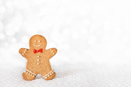 Gingerbread man on white background. Trendy Christmas minimal composition - homemade gingerbread man cookie, copy space.