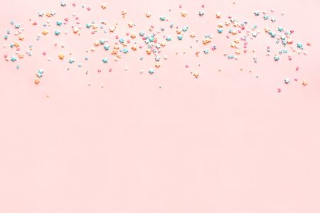 Colorful Pastel Sprinkles on pink background, top view, copy space. Sweet cake pastry ingredient, holiday birthday party and celebration concept, creative border.