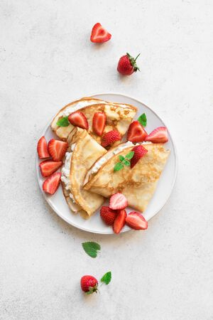 Crepes with ricotta cheese and fresh strawberries on white background, top view, copy space. Delicious crepes, thin pancakes.