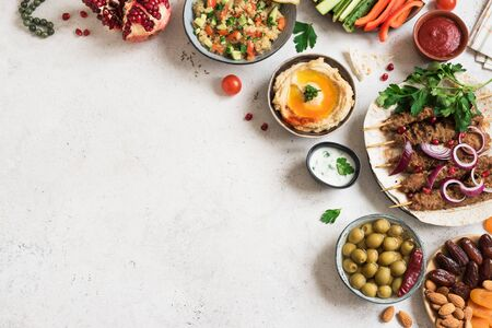 Arabic and Middle Eastern food, dinner table. Meat kebab, hummus, tabbouleh salad, traditional sauces, olives, pita,  dates fruits, nuts, pomegranate. Set of Arabian meal, top view, copy space.