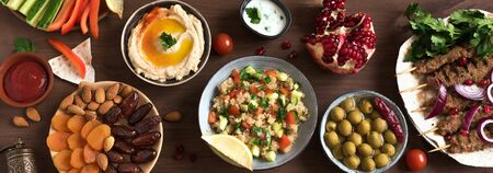 Middle Eastern Arabic food, dinner table. Meat kebab, hummus, tabbouleh salad, traditional sauces, olives, pita,  dates fruits, nuts, pomegranate. Set of Arabian meal, top view, banner.
