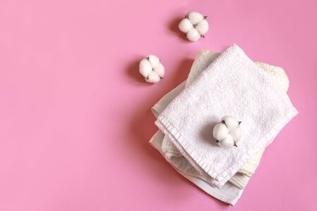 Stack of white cotton clothes and cotton flowers on pink background, flat lay, copy space. Organic cotton towels and clothes, eco lifestyle concept.