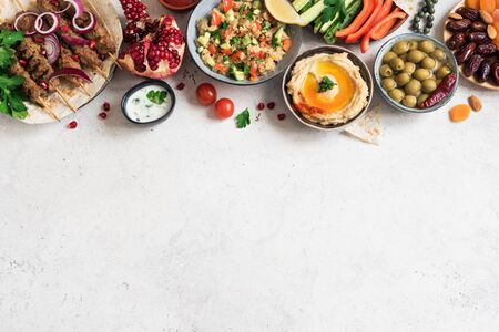 Arabic and Middle Eastern food, dinner table. Meat kebab, hummus, tabbouleh salad, traditional sauces, olives, pita,  dates fruits, nuts, pomegranate. Set of Arabian meal, top view, banner. Zdjęcie Seryjne