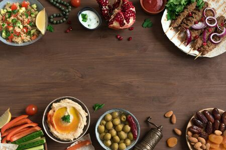 Middle Eastern Arabic food, dinner table. Meat kebab, hummus, tabbouleh salad, traditional sauces, olives, pita,  dates fruits, nuts, pomegranate. Set of Arabian meal, top view, copy space.