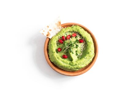 Green Avocado Hummus bowl, healthy vegan dip. Organic green herbal, spinach hummus,  spread  with pita bread isolated on white. Top view, copy space.