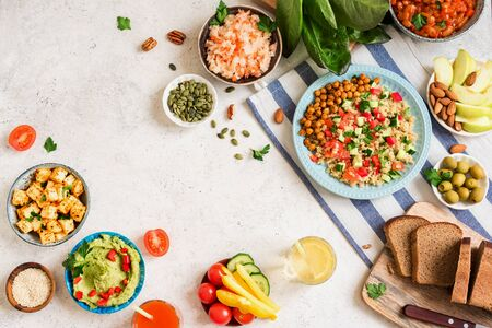 Vegan dinner table, set of healthy vegan vegetarian dishes for lunch - quinoa and chickpea salad, fried tofu, hummus dip, fruits, vegetables, nuts, seeds, top view, copy space, flat lay. Banque d'images