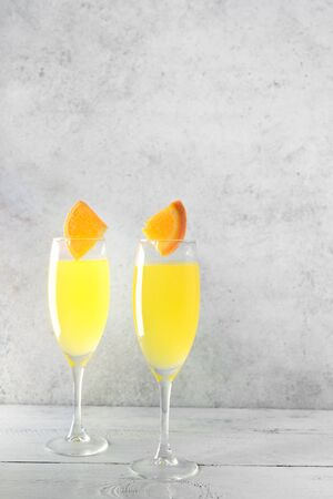 Mimosa cocktail with Champagne and Orange juice in flute glasses, copy space. Mocktail, Mimosa sparkling citrus drink. Archivio Fotografico