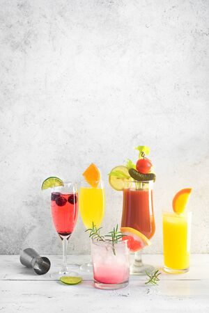 Brunch or Breakfast Cocktails Assortment. Bloody Mary, Mimosa drinks and various citrus alcohol refreshing cocktails on white table, copy space. Stock fotó