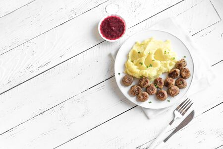 Traditional Swedish meatballs with mashed potato and lingonberry sauce, white wooden background with copy space. Roasted beef meatballs, scandinavian comfort food. Imagens