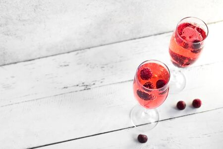 Kir Royal Champagne Cocktail on white, copy space. Flute glasses with berry sparkling champagne drink for celebrating or chilling. Stock fotó