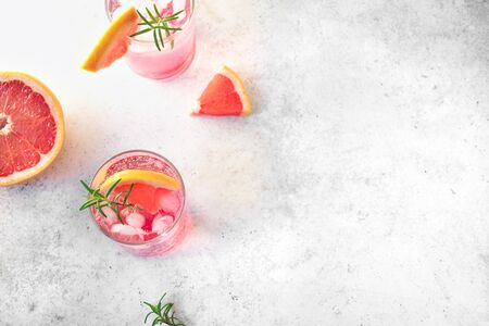 Grapefruit and rosemary cocktail, refreshing drink with ice. Greyhound cocktail, citrus sparkling soft drink, top view, copy space. Stock Photo
